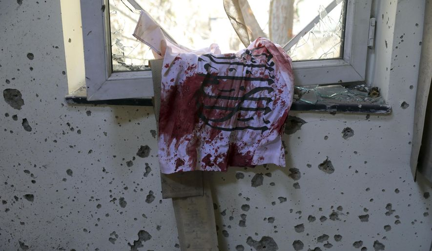 A blood-stained Taliban flag is seen on the window inside the Kabul University after a deadly attack in Kabul, Afghanistan, Tuesday, Nov. 3, 2020. The brazen attack by gunmen who stormed the university has left many dead and wounded in the Afghan capital. The assault sparked an hours-long gun battle. (AP Photo/Rahmat Gul)