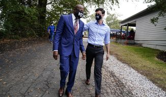 "Democratic candidate for Senate Jon Ossoff, right, and Democratic candidate for Senate Raphael G Warnock, left, arrive before they speak to a crowd during a ""Get Out the Early Vote"" event at the SluttyVegan ATL restaurant on Tuesday, Oct. 27, 2020, in Jonesboro, Ga. (AP Photo/Brynn Anderson)"
