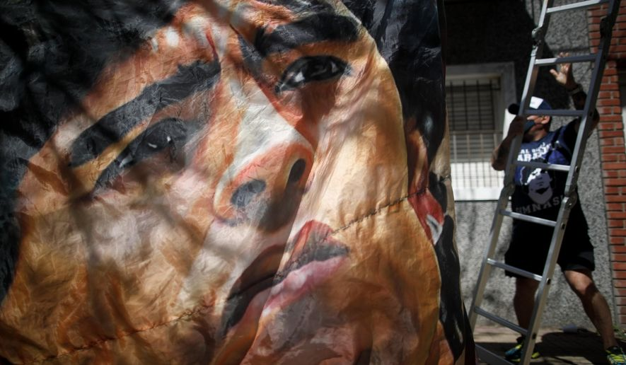 A banner of former soccer star Diego Maradona hangs outside the hospital where he is hospitalized in La Plata, Argentina, Tuesday, Nov. 3, 2020. Diego Maradona was admitted to the hospital with signs of depression Monday, three days after his 60th birthday. (AP Photo/Natacha Pisarenko)