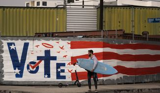 A man carries his surf board past a vote sign painted on a wall Monday, Nov. 2, 2020, in the Venice Beach section of Los Angeles. (AP Photo/Jae C. Hong)