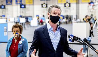 In this file photo, Gov. Gavin Newsom discusses the 2020 election while visiting the Golden State Warriors training facility, which is serving as a polling location, on Tuesday, Nov. 3, 2020, in Oakland, Calif. At left is Rep. Barbara Lee, D-Calif. (AP Photo/Noah Berger)  **FILE**