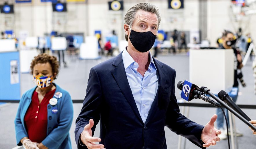 Gov. Gavin Newsom discusses the 2020 election while visiting the Golden State Warriors training facility, which is serving as a polling location, on Tuesday, Nov. 3, 2020, in Oakland, Calif. At left is Rep. Barbara Lee, D-Calif. (AP Photo/Noah Berger)