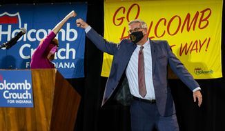 Indiana Gov. Eric Holcomb gets a high five from Lt. Gov. Suzanne Crouch after he addressed supporters after winning his second term as governor in Indianapolis, Tuesday, Nov. 3, 2020. (AP Photo/Michael Conroy)