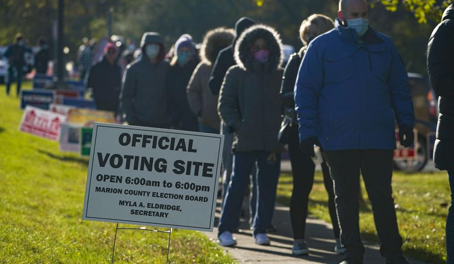 Voters wait in a line to cast their ballot at a polling place in Indianapolis, Tuesday, Nov. 3, 2020. (AP Photo/Michael Conroy)