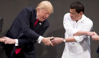 In this Nov. 13, 2017, file photo, U.S. President Donald Trump, left, reacts as he does the 'ASEAN-way handshake' with Vietnamese Prime Minister Nguyen Xuan Phuc, not pictured, and Philippine President Rodrigo Duterte on stage during the opening ceremony at the ASEAN Summit at the Cultural Center of the Philippines, in Manila. The 2020 ASEAN Summit is being conducted virtually but Mr. Trump is not in attendance this year. (AP Photo/Andrew Harnik, File)