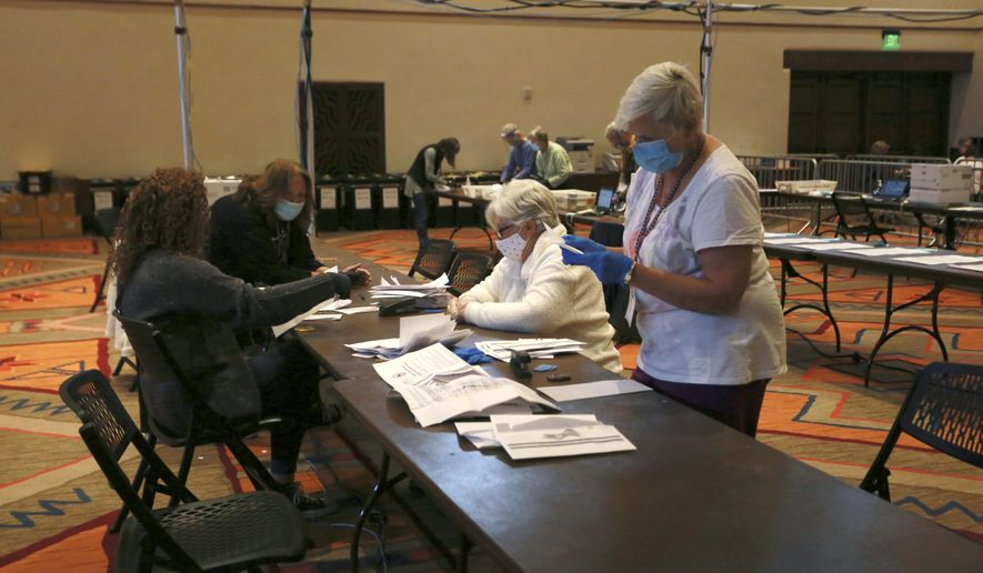 Election workers sort electronically submitted ballots at the Santa Fe Convention Center on Election Day, Tuesday, Nov. 3, 2020, in Santa Fe, N.M.  (AP Photo/Cedar Attanasio)