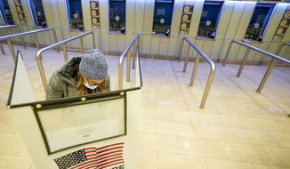 A voter marks her ballot during the first hour of voting in New York at Madison Square Garden, Tuesday, Nov. 3, 2020. (AP Photo/Mary Altaffer)