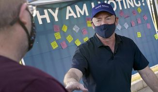 Mark Kelly, Democratic candidate for the U.S. Senate, greets voters at a polling station early, Tuesday, Nov. 3, 2020, in Phoenix. Kelly is seeking to unseat incumbent Martha McSally. (AP Photo/Matt York)