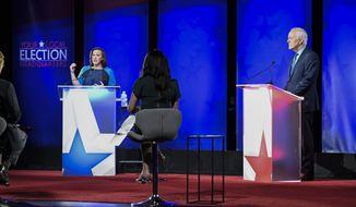 MJ Hegar, of Round Rock, left, speaks during a debate with Republican U.S. Sen. John Cornyn, of Texas, right, Friday, Oct. 9, 2020, in Austin, Texas. (Bob Daemmrich/Nexstar/KXAN via AP, Pool)