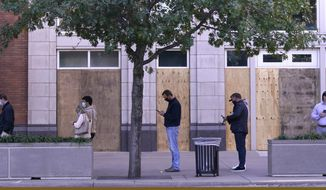 Windows are boarded up as voters line up outside the American Airlines Center in downtown Dallas waiting to cast their ballots on Election Day Tuesday, Nov. 3, 2020, in Dallas. (AP Photo/LM Otero)