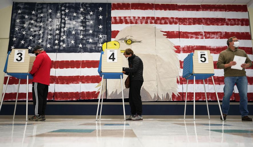 In this file photo, voters cast their ballots under a giant mural at Robious Elementary School in Midlothian, Va., Tuesday Oct. 3, 2020. Poll workers said that traffic was slow due to all the early voting in the precinct. (AP Photo/Steve Helber)  **FILE**