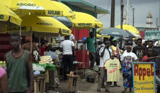 """Street vendors use parasols reading """"Abobo ADOland"""" in reference to the Ivory Coast President Alassane Ouattara, who is known as ADO, at Abobo neighborhood in Abidjan, Ivory Coast, Monday, Nov. 2, 2020. International election observers in Ivory Coast said Monday that voter turnout was """"extremely low"""" in parts of the country after leading opposition candidates called for a boycott to protest President Alassane Ouattara's bid for a controversial third term. (AP Photo/Leo Correa)"""