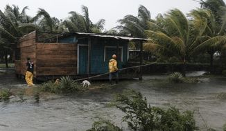 Two men walk around the perimeters of a home surrounded by flood waters brought on by Hurricane Eta in Wawa, Nicaragua, Tuesday, Nov. 3, 2020. Eta slammed into Nicaragua's Caribbean coast with potentially devastating winds Tuesday, while heavy rains thrown off by the Category 4 storm already were causing rivers to overflow across Central America. (AP Photo/Carlos Herrera)