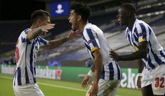 Porto's Luis Diaz celebrates with Otavio, left, and Malang Sarr, right, after scoring his side's third goal during the Champions League group C soccer match between FC Porto and Olympique de Marseille at the Dragao stadium in Porto, Portugal, Tuesday, Nov. 3, 2020. (AP Photo/Luis Vieira)