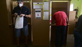 Voters use booths to mark their ballots for the general election at a polling center set up at the Rafael Labra School in San Juan, Puerto Rico, Tuesday, Nov. 3, 2020.  In addition to electing a governor, Puerto Ricans are voting in a non-binding referendum on statehood. (AP Photo/Carlos Giusti)