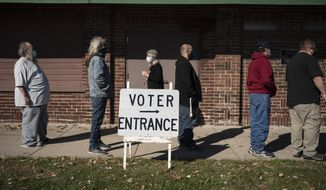 Voters wait in line outside a polling center on Election Day, Tuesday, Nov. 3, 2020, in Kenosha, Wis. (AP Photo/Wong Maye-E)