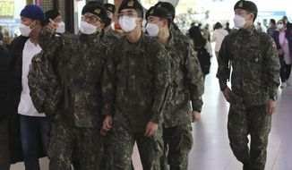 Army soldiers wearing face masks to help protect against the spread of the coronavirus arrive to board a train at the Seoul Railway Station in Seoul, South Korea, Tuesday, Nov. 3, 2020. (AP Photo/Ahn Young-joon)