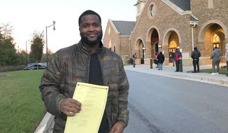Justin Windom prepares to cast his vote Tuesday, Nov. 3, 2020 in Atlanta, Ga. Windom is voting for former Vice President Joe Biden. Windom said he liked Biden's work with Obama in the previous administration, and his vice presidential nominee, Kamala Harris. (AP Photo/Haleluya Hadero)