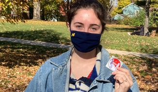 Georgia Richardson-Smaller shows off her I Voted sticker Tuesday, Nov. 3, 2020 in Ann Arbor, Mich. Smaller, an undergraduate who wore a mask with Michigan's block 'M' on it, said she voted for Biden. She cited health care, equality and police brutality as the most important issues facing the country. (AP Photo/Noah Trister)