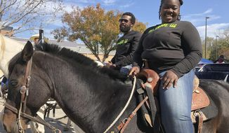 """Eboni Price, right, used a different form of transportation to get to her polling site Tuesday, Nov. 3, 2020 in Houston, Texas, her trusty horse Moon. """"My people went through a lot of things to have the right to vote,"""" Price said. """"I can exercise my right to vote on horseback so I'm riding to vote."""" Price, who is also studying to be a veterinarian, said she voted for Kanye West in the presidential race. (AP Photo/Juan Lozano)"""