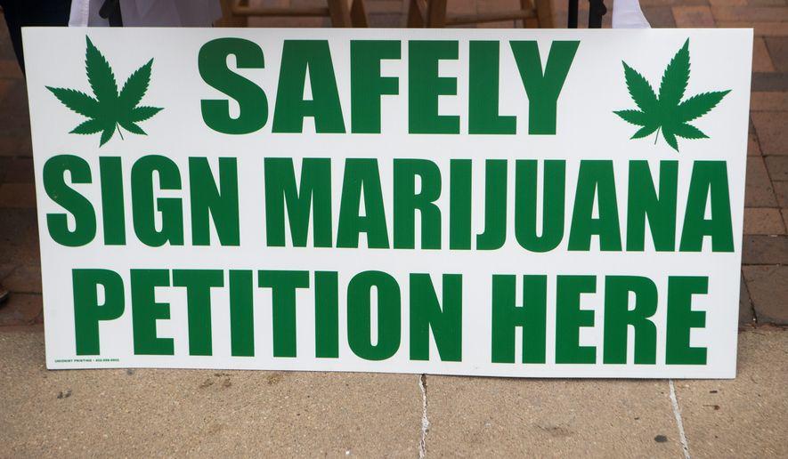 Riley Slezak and Nebraska State Senator Adam Morfeld collect signatures for the 2022 medical marijuana petition outside of the Tavern on the Square on Saturday, Oct. 24, 2020, in Lincoln, Nebraska. (Kenneth Ferriera/Lincoln Journal Star via AP)