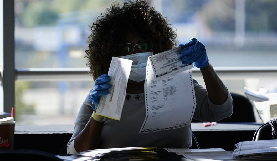 An election personnel examines a ballot as vote counting in the general election continues at State Farm Arena, Wednesday, Nov. 4, 2020, in Atlanta. (AP Photo/Brynn Anderson)