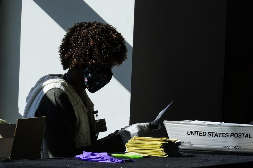 An election worker counts ballots at State Farm Arena on Wednesday, Nov. 4, 2020, in Atlanta. (AP Photo/Brynn Anderson)