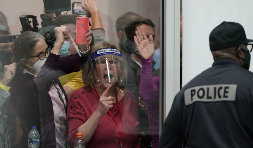 Election challengers yell as they look through the windows of the central counting board as police were helping to keep additional challengers from entering due to overcrowding, Wednesday, Nov. 4, 2020, in Detroit. (AP Photo/Carlos Osorio)
