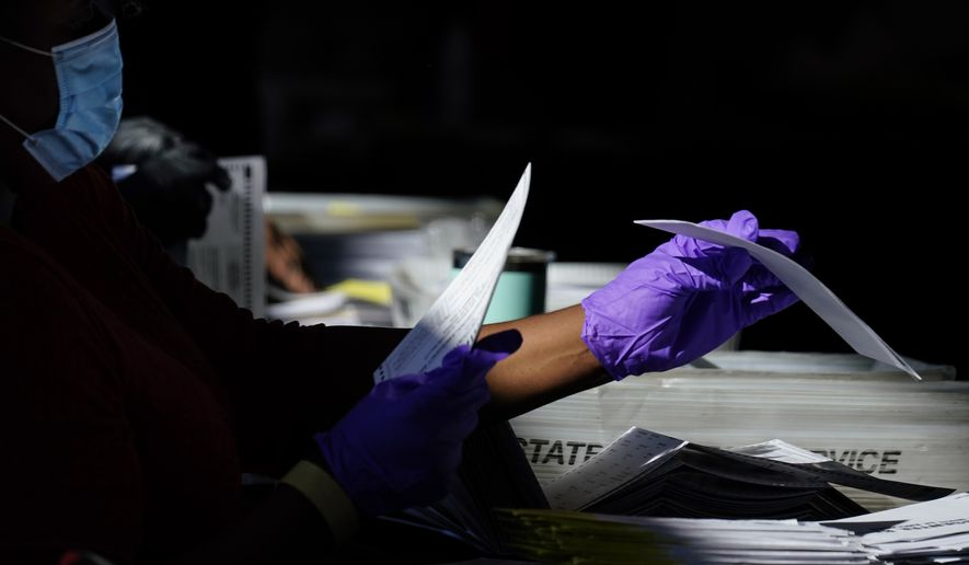 An election personnel counts ballots as votes are counted at State Farm Arena on Wednesday, Nov. 4, 2020, in Atlanta. (AP Photo/Brynn Anderson)