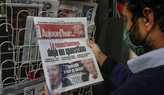A man wearing a face mask as a precaution against the coronavirus reads the headlines about the U.S. presidential elections at a newspapers stand in Paris, Wednesday, Nov. 4, 2020. The world is watching as millions of Americans cast their ballots for the next president on Tuesday. (AP Photo/Michel Euler)