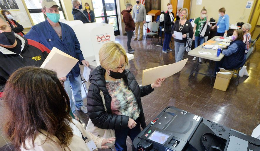Voter Kari Ackerman, center, casts her ballot with help from poll worker Brenda Anderson, left, at the Girard Borough Building on Tuesday, Nov. 3, 2020, in Erie, Pa. (Greg Wohlford/Erie Times-News via AP) ** FILE **