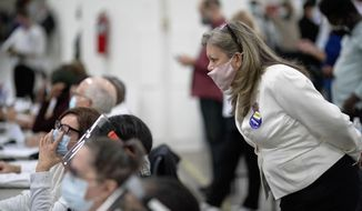A Republican election challenger at right watches over election inspectors as they examine a ballot as votes are counted into the early morning hours Wednesday, Nov. 4, 2020, at the central counting board in Detroit. (AP Photo/David Goldman)