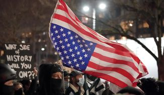 A person carries an upside down flag as people march on the night of the election in Seattle, Tuesday, Nov. 3, 2020. (AP Photo/Ted S. Warren)
