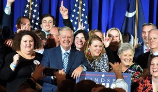 Supporters pose with U.S. Sen. Lindsey Graham, center, following his victory speech after winning another term in office on Tuesday, Nov. 3, 2020, in Columbia, S.C. (AP Photo/Meg Kinnard)