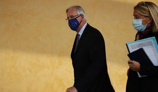 European Commission's Head of Task Force for Relations with the United Kingdom Michel Barnier, left, leaves the European Commission headquarters in Brussels, Wednesday, Nov. 4, 2020. Barnier on Wednesday briefed the European Union ambassadors on the state of negotiations with the United Kingdom, as both sides continue to struggle to find common ground on a free trade deal which needs to be in place by Jan. 1. (AP Photo/Francisco Seco)