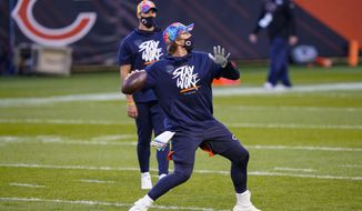 Chicago Bears quarterback Nick Foles throws as Mitchell Trubisky watches before the team's NFL football game against the Tampa Bay Buccaneers in Chicago, Thursday, Oct. 8, 2020. (AP Photo/Charles Rex Arbogast)