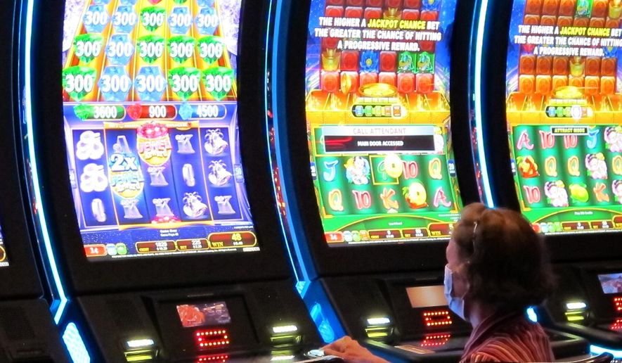 A woman plays a slot machine at the Golden Nugget casino in Atlantic City, N.J. on July 2, 2020. The U.S. gambling industry was a big winner at the polls on Nov. 3, 2020, with three states authorizing sports betting and three others either authorizing or expanding casino gambling. (AP Photo/Wayne Parry)  **FILE**