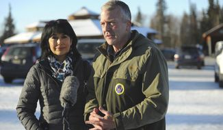 Incumbent Republican Sen. Dan Sullivan, left, with his wife Julie, speaks to the media after casting his ballot at the Alaska Zoo Tuesday, Nov. 3, 2020 in Anchorage, Alaska. (AP Photo/Michael Dinneen)