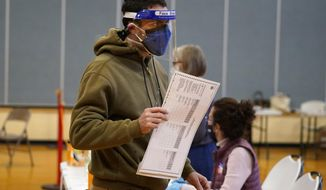 Julian St. Laurent wear a face shield and two face masks to help prevent the spread of the coronavirus as he walks to a voting both to cast his ballot to vote on Election Day Tuesday, Nov. 3, 2020, in Portland, Maine.  (AP Photo/Robert F. Bukaty)