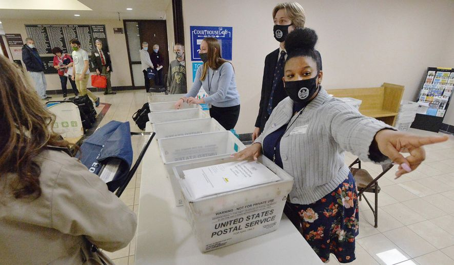 Marian Collin Franco, 20, helps collect provisional ballots at the Erie County Courthouse on Election Day, Tuesday, Nov. 3, 2020, in Erie, Pa. (Greg Wohlford/Erie Times-News via AP)