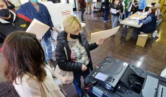 Voter Kari Ackerman, center, casts her ballot with help from poll worker Brenda Anderson, left, at the Girard Borough Building on Tuesday, Nov. 3, 2020, in Erie, Pa. (Greg Wohlford/Erie Times-News via AP)
