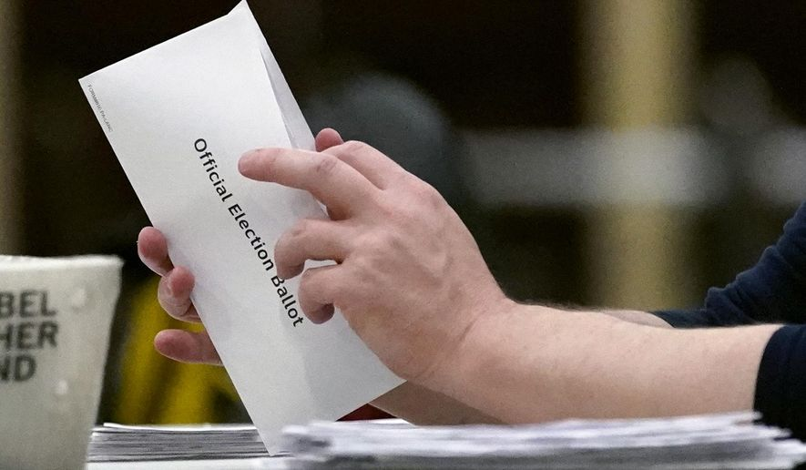A worker opens a mail-in ballot to prepare it for counting, Wednesday, Nov. 4, 2020, at the convention center in Lancaster, Pa., following Tuesday's election. (AP Photo/Julio Cortez)