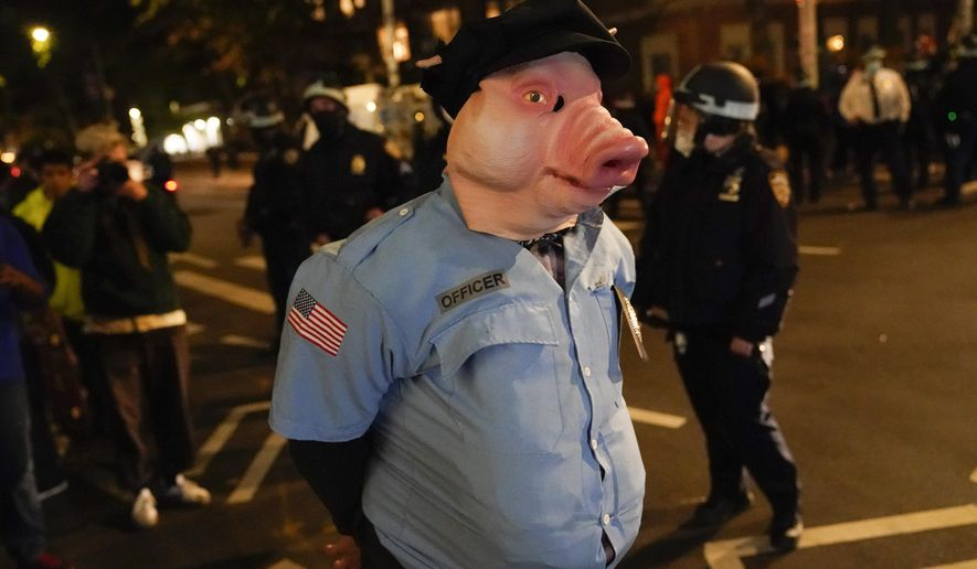 A demonstrator, dressed as a police officer wearing a pig mask, walks through the streets around Washington Square Park, Wednesday, Nov. 4, 2020, in New York. (AP Photo/Seth Wenig)
