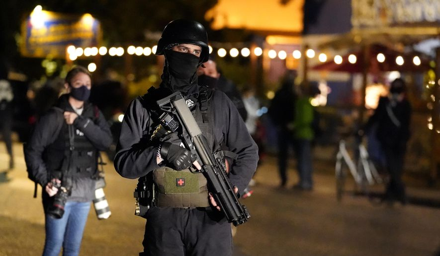 A person carries a gun while marching on the night of the election, Tuesday, Nov. 3, 2020, in Portland, Ore. (AP Photo/Marcio Jose Sanchez)