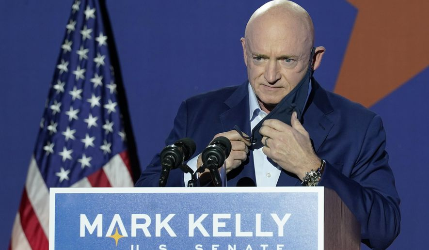 Mark Kelly, Arizona Democratic candidate for U.S. Senate, removes his mask as he prepares to speak at an election night event Tuesday, Nov. 3, 2020 in Tucson, Ariz. (AP Photo/Ross D. Franklin)