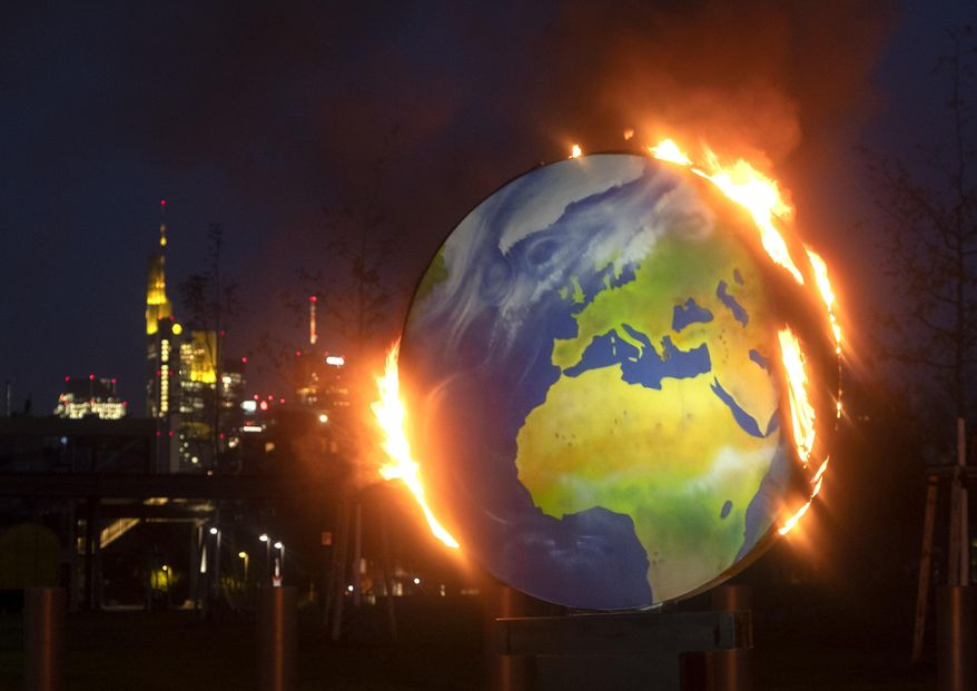 """A makeshift globe burns in front of the European Central Bank in Frankfurt, Germany, Wednesday, Oct. 21, 2020. Activists of the so-called """"KoalaKollektiv"""", an organization asking for climate justice, protested with the burning of the globe against the ECB's climate policy. (AP Photo/Michael Probst)"""