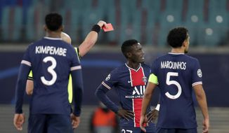 Referee Szymon Marciniak shows a red card to PSG's Idrissa Gueye, second right, during the Champions League group H soccer match between RB Leipzig and Paris Saint Germain at the RB Arena in Leipzig, Germany, Wednesday, Nov. 4, 2020. (AP Photo/Michael Sohn)