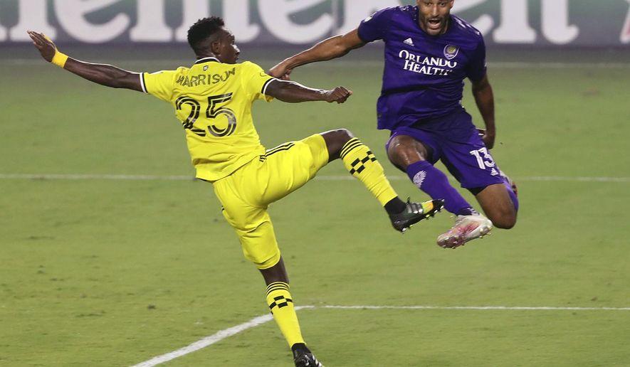 Orlando City's Tesho Akindele (13) leaps beside Columbus Crew's Harrison Afful (25) during an MLS soccer game, Wednesday, Nov. 4, 2020, in Orlando, Fla. (Stephen M. Dowell/Orlando Sentinel via AP)