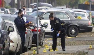 Members of the Oakland Police Department investigate the scene of an officer involved shooting on Wednesday, Nov. 4, 2020, in Oakland, Calif. Police say at least two police officers were injured and a person was shot by police during a robbery at a marijuana business. (Aric Crabb/Bay Area News Group via AP)