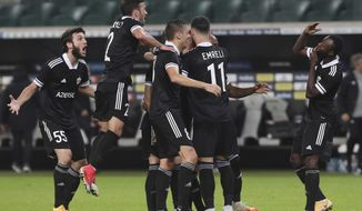 Filip Ozobic, center, with team celebrates after scoring a goal during the UEFA Europa League fourth round qualifying soccer match between Legia Warsaw and Qarabag, in Warsaw, Poland, Thursday, Oct. 1, 2020.(AP Photo/Czarek Sokolowski)